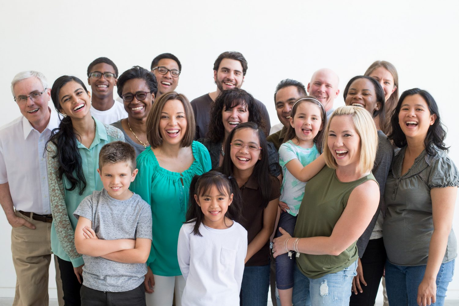 A multi-ethnic group of multiple generations are standing together for a family reunion. They are happily laughing and smiling while looking at the camera.